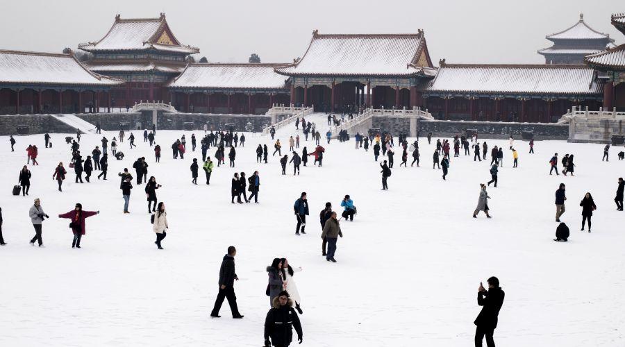 Gente camina por la nieva frente a la Ciudad Prohibida de Beijing. (Foto: AFP)